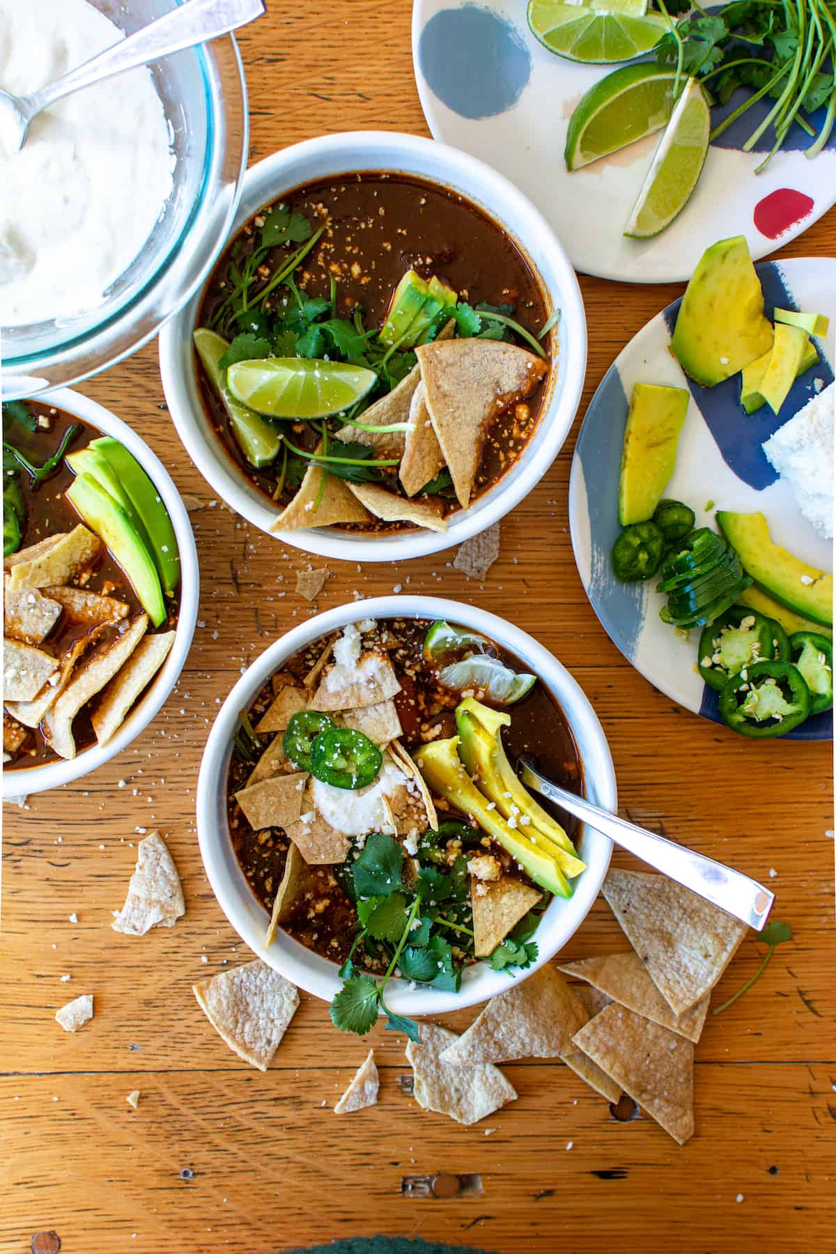 Overhead image of two bowls of chicken tortilla soup garnished with avocado, cilantro, and lime sitting on a wood table.