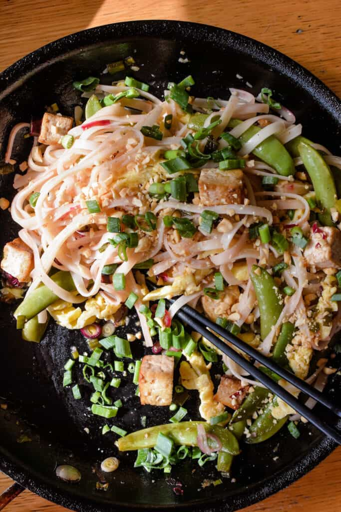 Black frying pan with tofu pad Thai and black chopsticks.