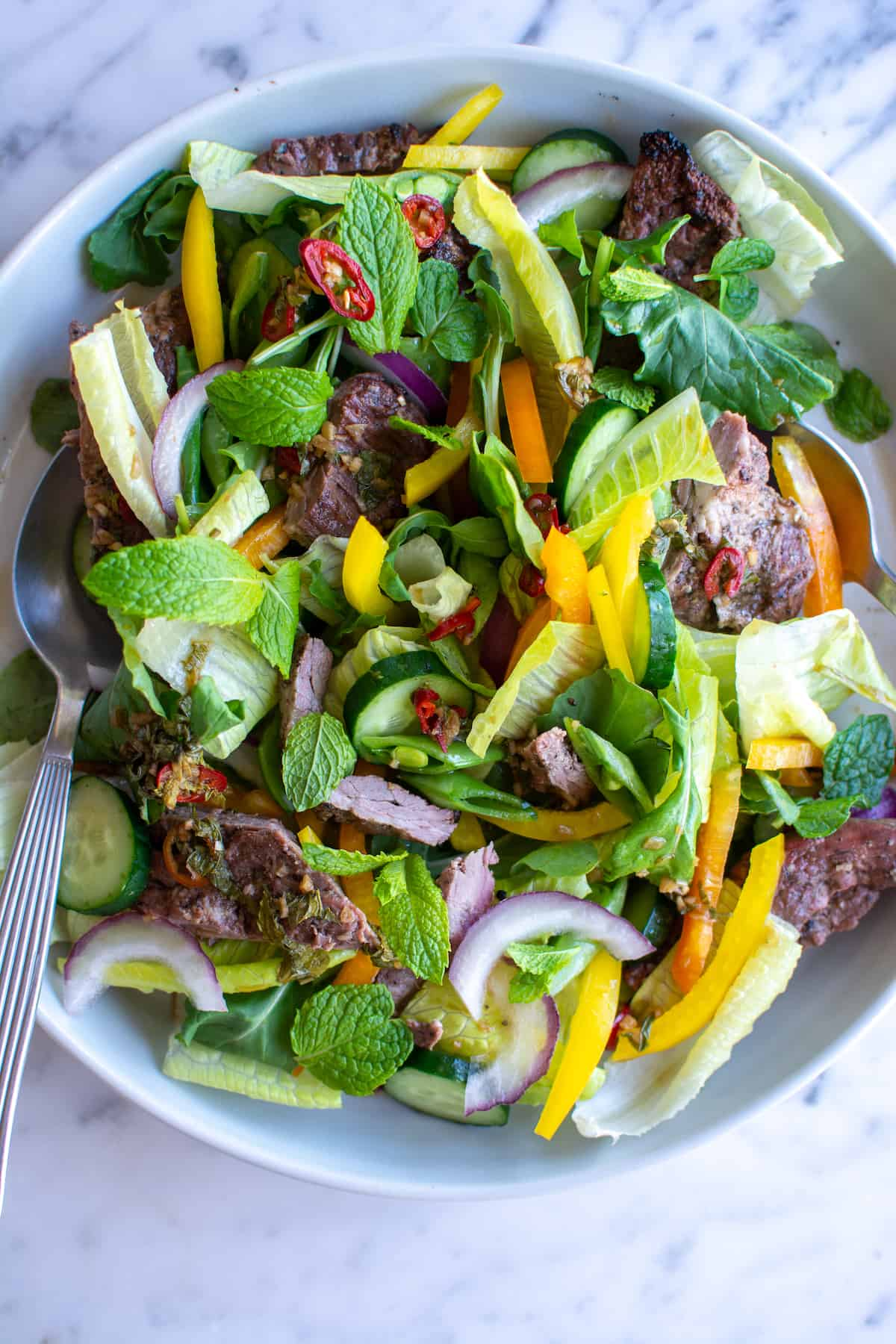 A platter of Thai Steak Salad sitting on a marble table with two spoons on each side.