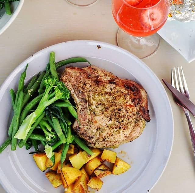These Cilantro-Garlic Pork Chops are super easy and really delicious. Coated in a flavor-packed marinade and grilled they are the perfect dinner. #porkchops #grill #grilledporkchops #boneinporkchops #easyporkchops