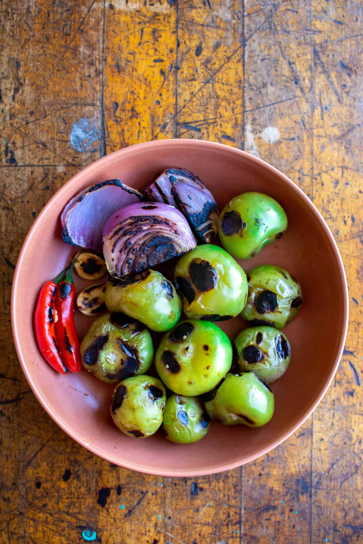 A brown bowl sitting on a wood table with charred tomatillos, red onions, and red jalapeños in it.