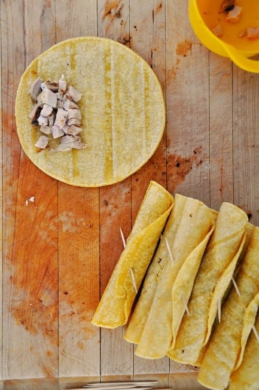 Corn tortilla on a wooden cutting board with pork on top.