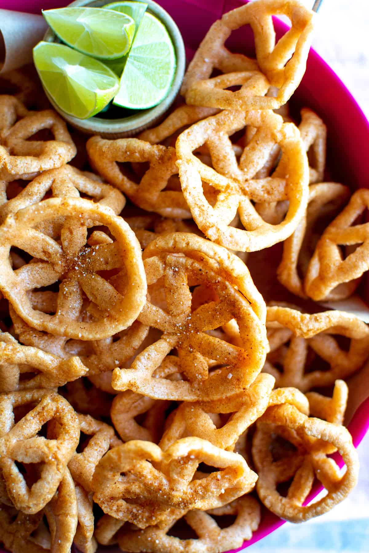Close up image of chicharrones de harina with chili spice mix on them and lime wedges on the side.