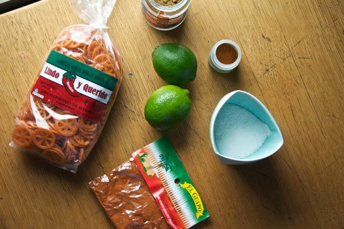 A bag of chicharrones de harina, chili powder, a bowl of salt, limes, and jars of spices on a wooden table.