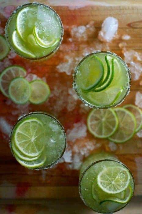 Overhead image of cucumber margaritas sitting on a wood cutting board with ice all around.