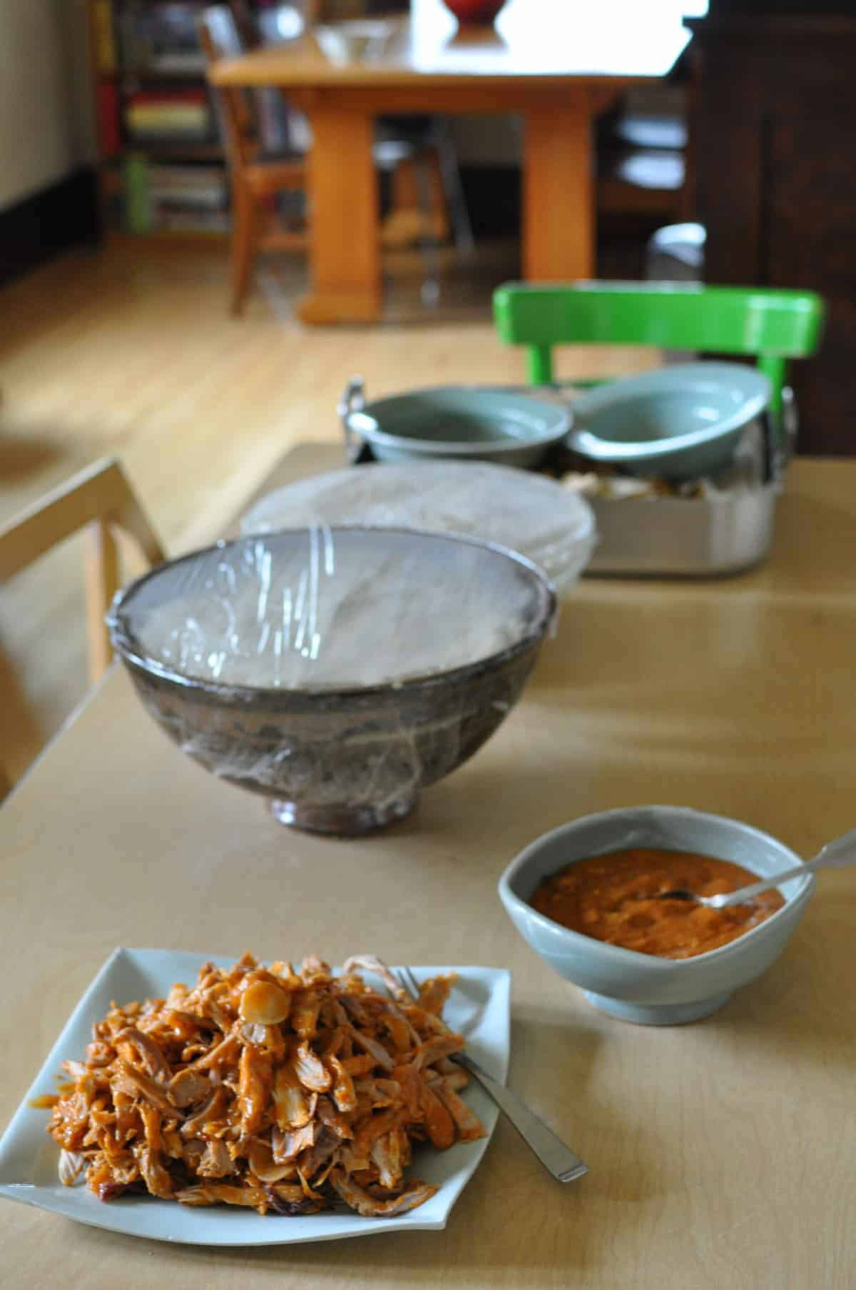 A table set with all the ingredients for making pork tamales. A plate of shredded pork, mole sauce, and masa.