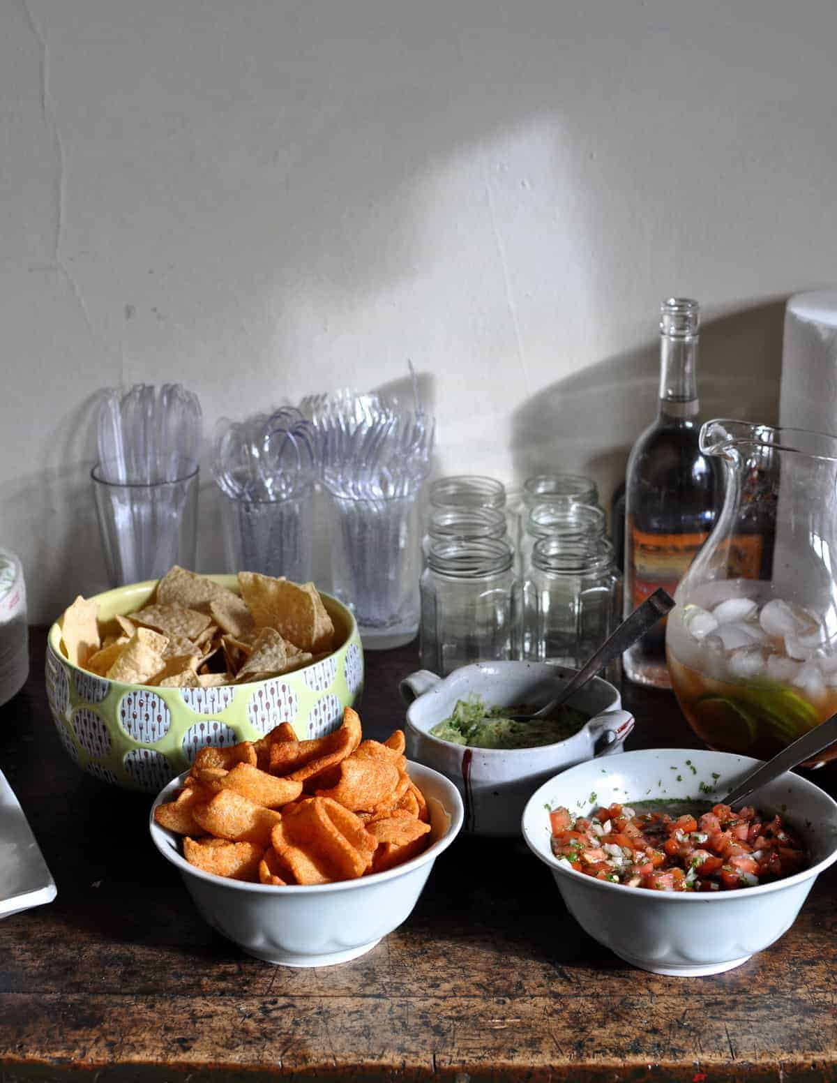 A table set with snacks and drinks for a tamalada. A yellow bowl of tortilla chips and two bowls of salsa.