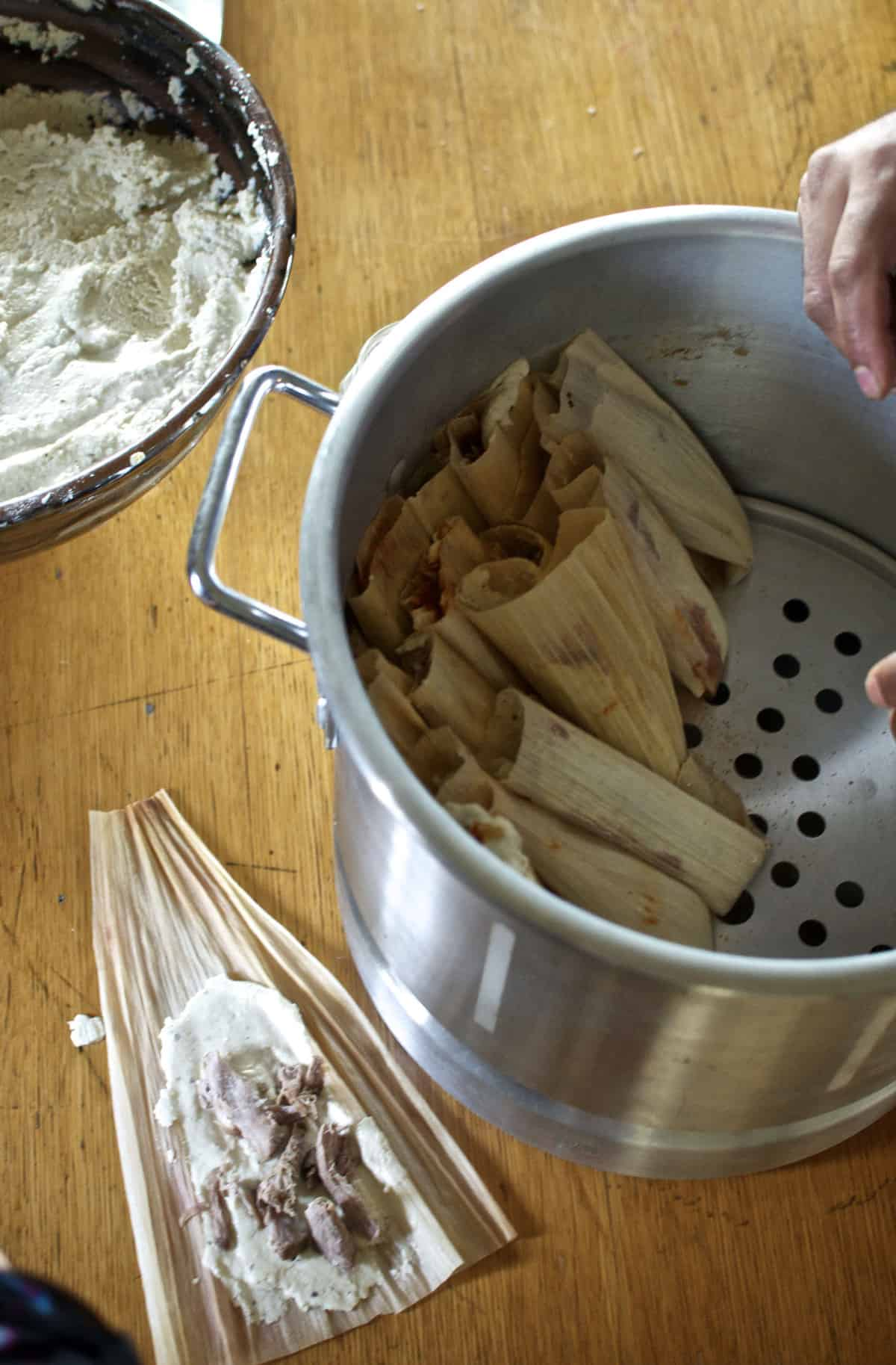 A big pot with tamales inside and a tamal being assembled sitting next to it on a wooden table.