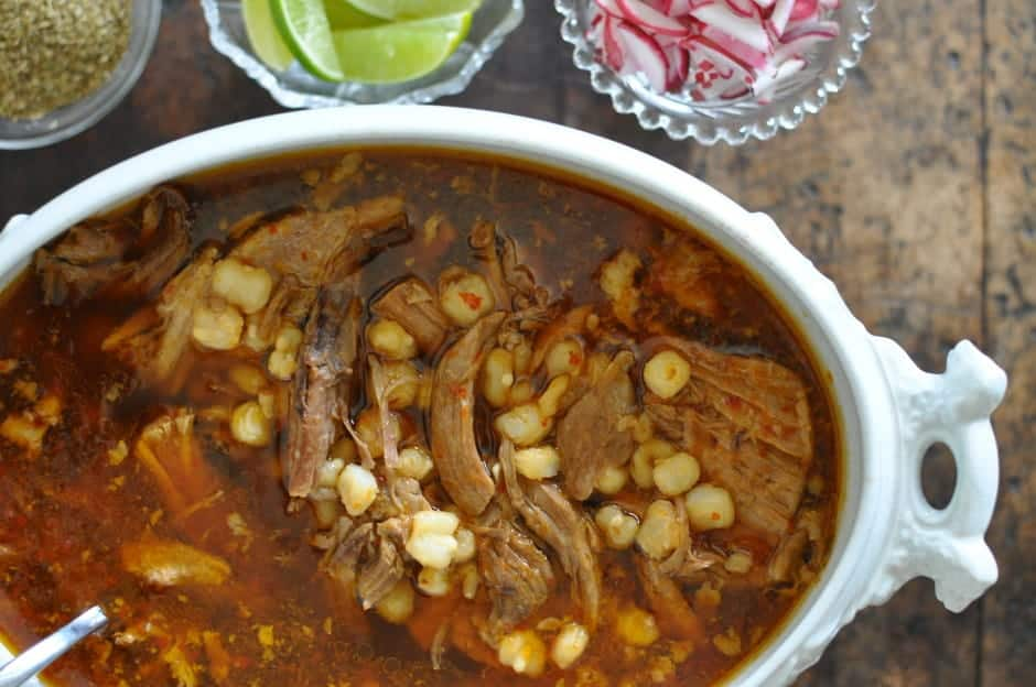A classic Pozole Rojo recipe with tender pork, hominy, and red chile broth. Top the stew with sliced radishes, dried oregano, and chopped onion. Dairy-free!