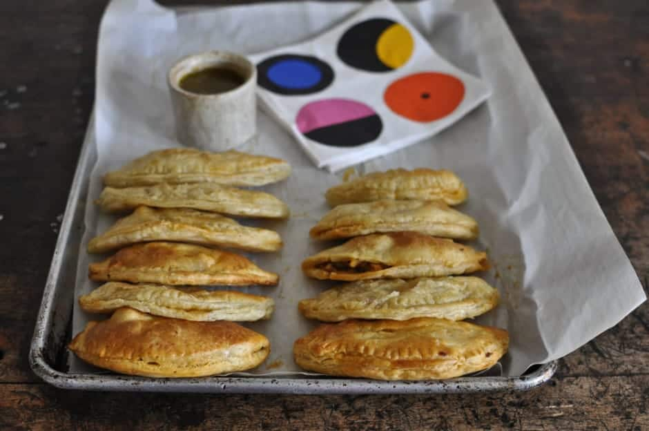 Easy chicken empanadas made wrapped in store-bought puff pastry so you don't have to make the dough. Serve with a garlic mojo sauce for a weeknight dinner!