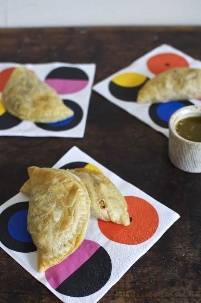 Chicken hand pies on colorful napkins sitting on a wooden counter.
