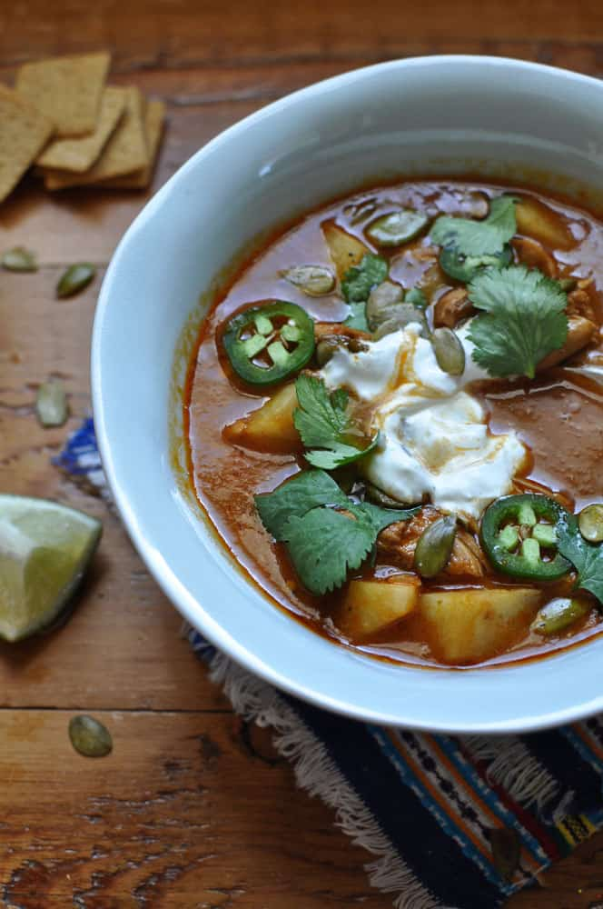 An overhead image of a bowl of chileatole soup with a dollop of sour cream, cilantro, and jalapeno slices.