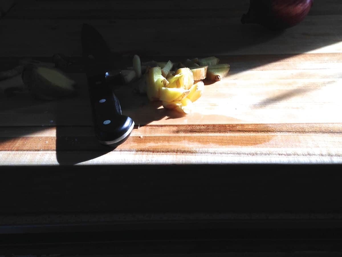A shadowy image of ginger sliced on a wood cutting board with a knife near by.