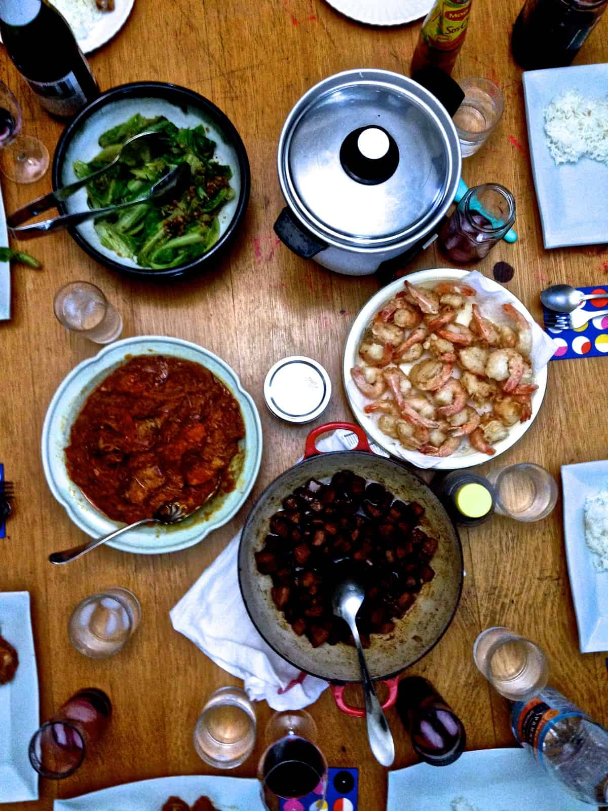 An overhead image of a wood table set for dinner with several different dishes on the table.