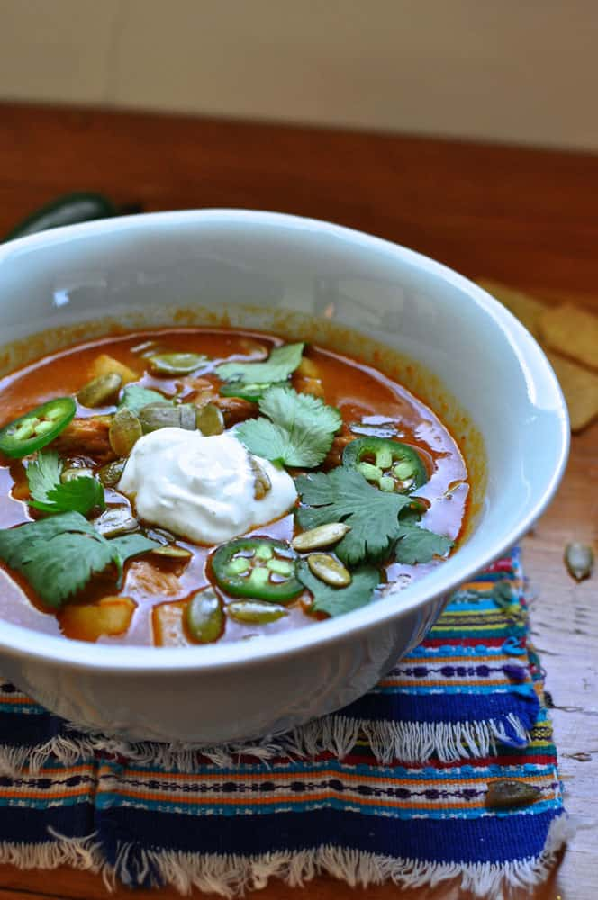 A bowl of red chileatole soup topped with a dollop of sour cream, cilantro leaves, and jalapeno slices.