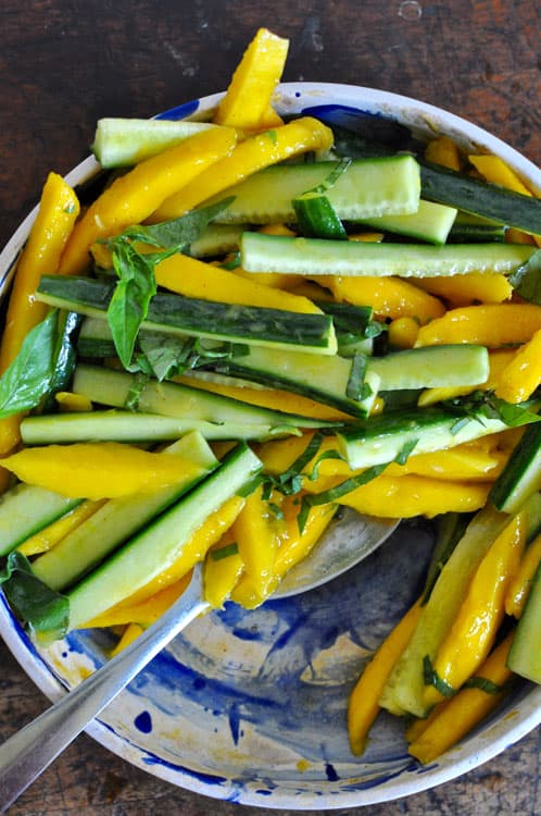 Mango-Cucumber Salad arranged in a blue and white bowl sitting on a wooden table with a spoon.