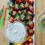 Long tray of sour cream fruit dip and cut up fruit