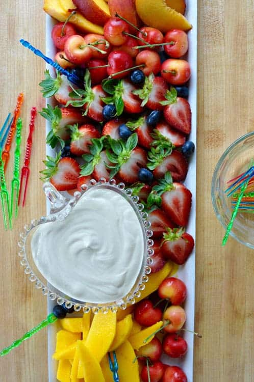 Long tray of cut up fruit with a heart-shaped bowl of sour cream fruit dip.