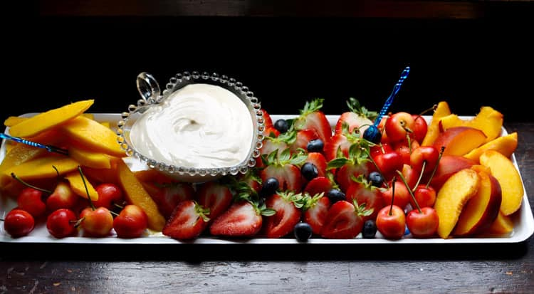 Long tray of various cut-up fruits sitting on a wooden table with a heart-shaped bowl of sour cream.