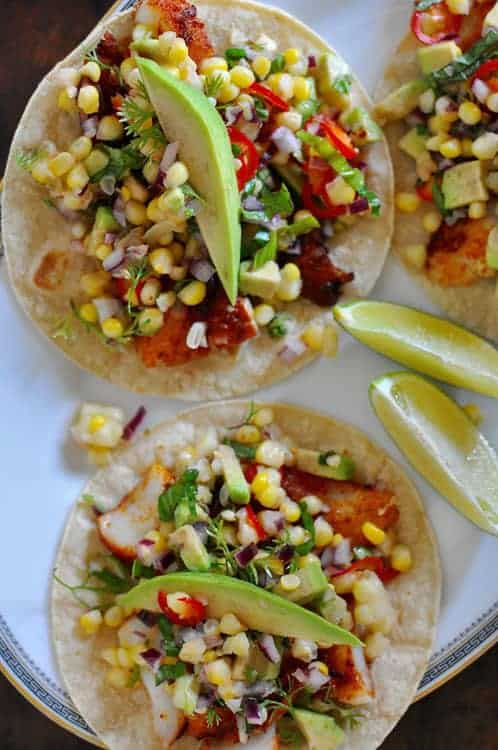 A terrific grilled fish tacos recipe topped with fresh sweet corn salsa and avocado slices. This super healthy dinner is perfect for summer. Gluten-free!