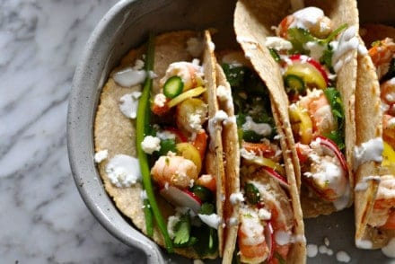 These weeknight shrimp tacos are marinated in garlic and black pepper. Dress them up with as many garnishes as you'd like for an easy weeknight dinner.