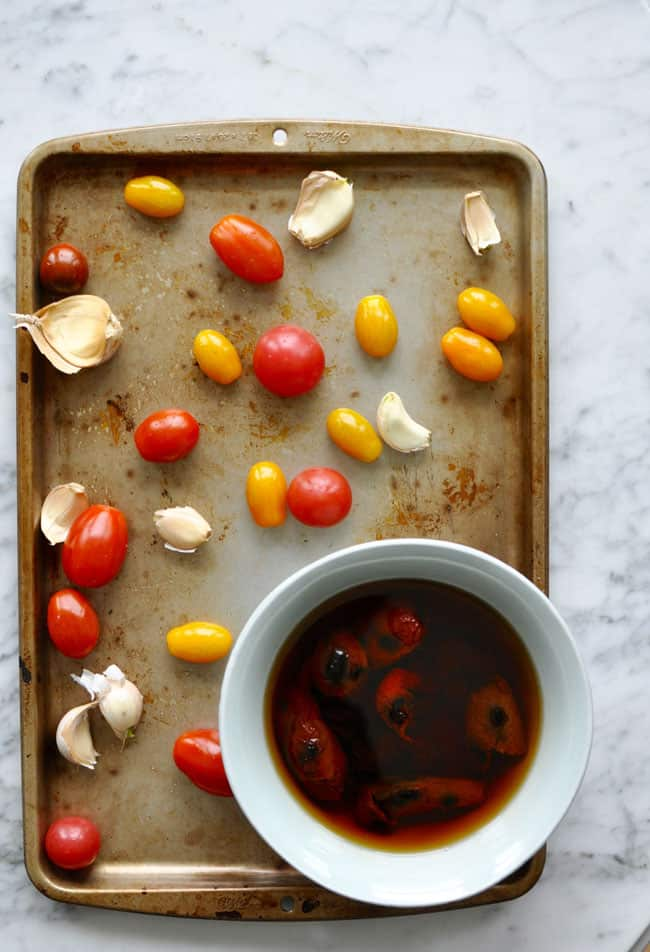 Garlic and cherry tomatoes sitting on a baking sheet with a bowl of morita chiles soaking in water.