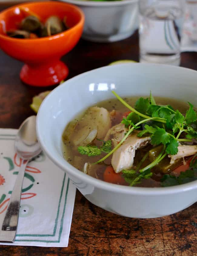 A bowl of chicken soup sitting on a wood table with cilantro leaves on top and a napkin with a spoon resting on it to one side.