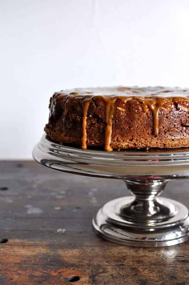 This beautiful bananas foster cake is flavored with coffee and walnuts and sour cream then topped with bananas and a spiced rum dulce de leche caramel.