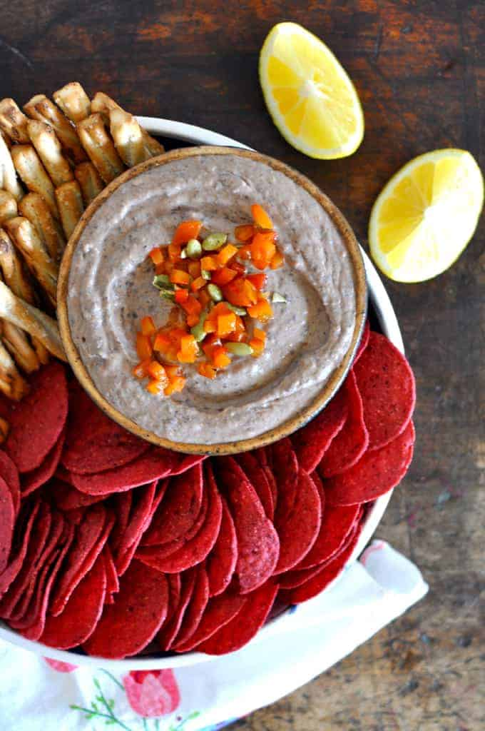 Sweet roasted red peppers and roasted garlic meet the earthy richness of black beans in this most untraditional but delicious black bean hummus recipe.