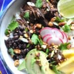 Bowl of cooked beef, black beans, avocado and radish with chopped nuts on top.