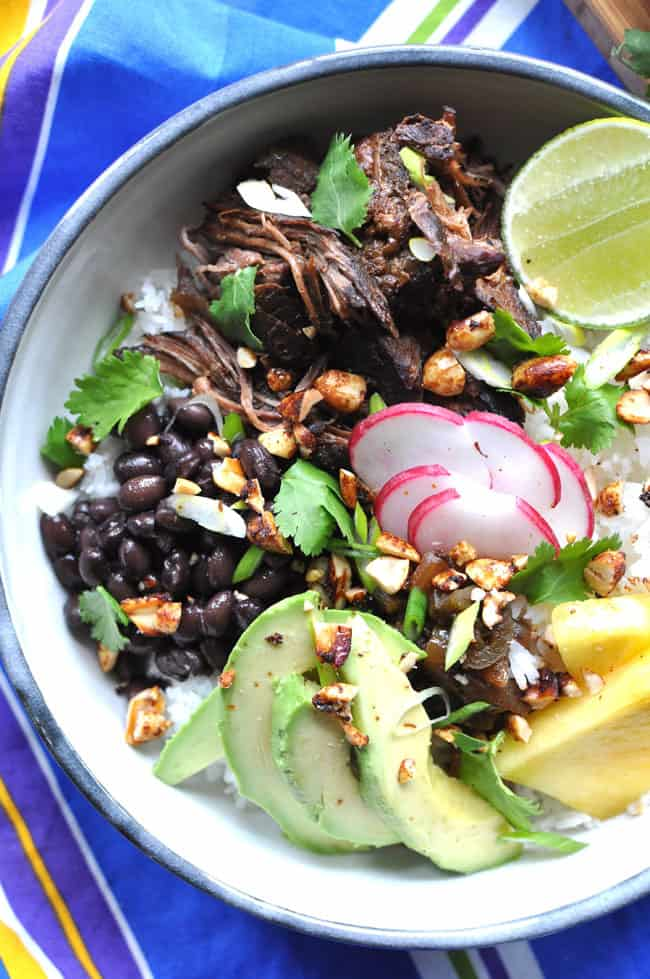 A bowl of rice with Carne Adobada on top and black beans sitting on a striped blue tablecloth.