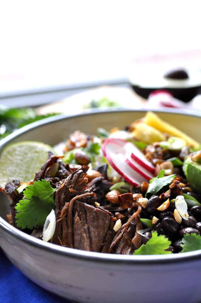 Pieces of cooked beef in a bowl with cilantro, radishes, and chopped peanuts.