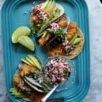 A blue tray holding fish tacos with a dish of radish pico de Gallo and limes.