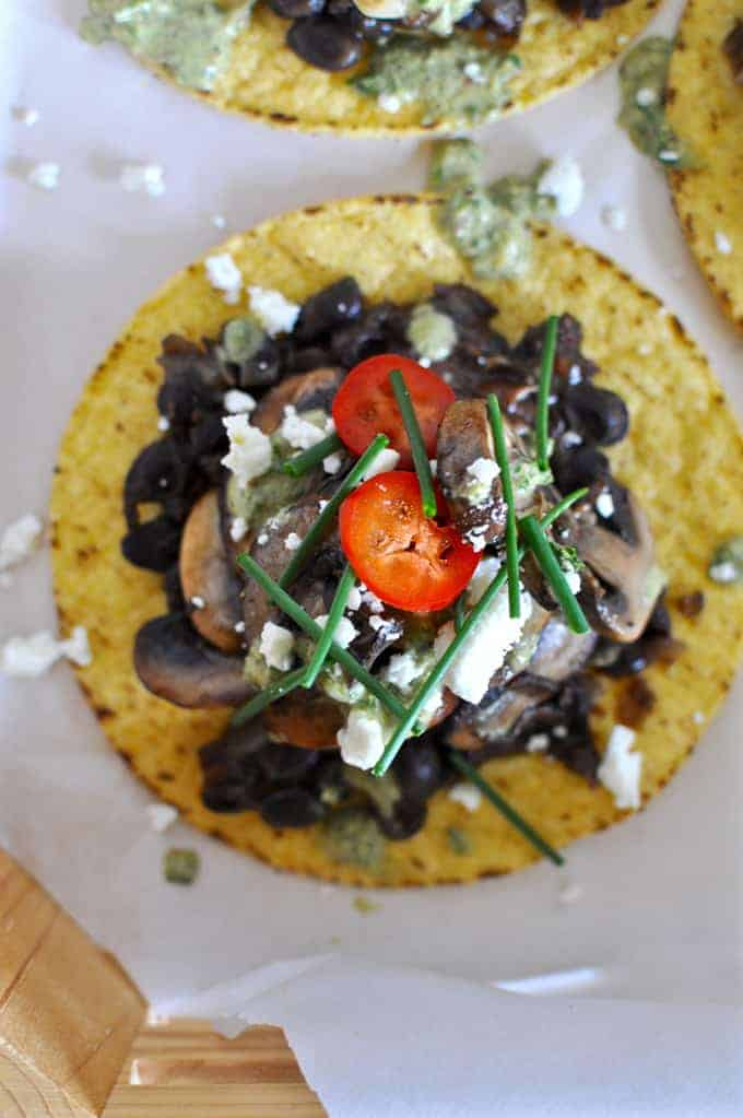 Mexican Meatless Mondays are made for Mushroom Tostadas! Crispy tortillas piled with black beans, caramelized mushrooms, feta, and a charred scallion pesto.