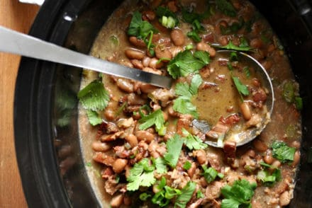 Crock pot with frijoles borrachos and cilantro.