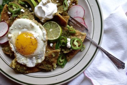 Green chilaquiles are green salsa soaked tortilla chips topped with Cotija cheese, sour cream, jalapeños, sliced radishes, scallions, and a fried egg.