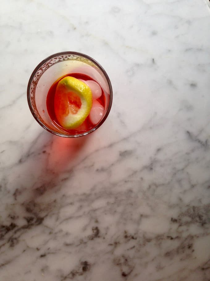 Campari Wine Cocktail in a glass with ice and lemon slices sitting on a marble table.