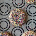 Sprinkle cookies on a mat with black circles on it.
