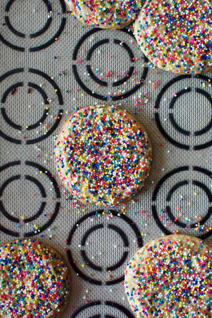 Sprinkle cookies sitting on a baking mat with black circles on it.