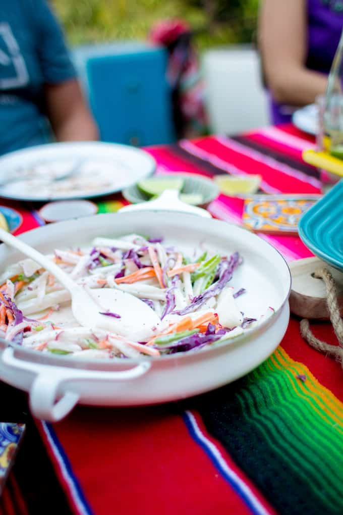 A white serving dish with salad in it sitting on a colorful serape table cloth.