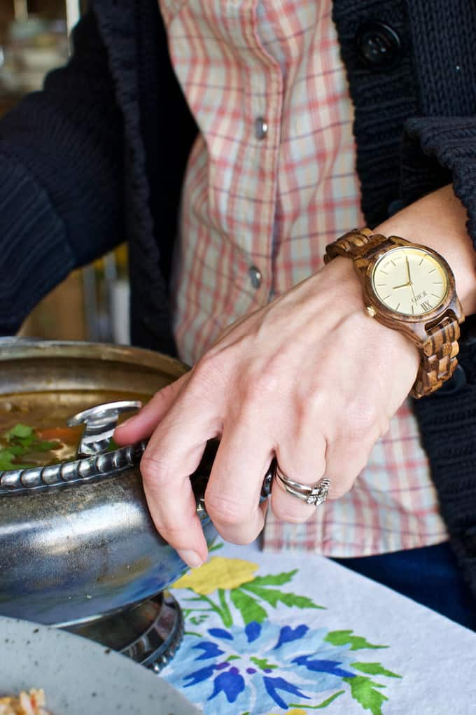 A woman wearing a watch, a pink plaid shirt and a black sweater bringing a soup terrine to the table.