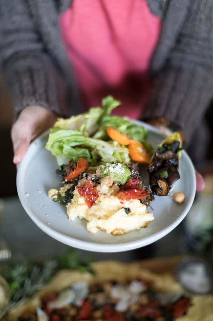 A person holding a plate of polenta with salad on the side and tomato sauce on the polenta.