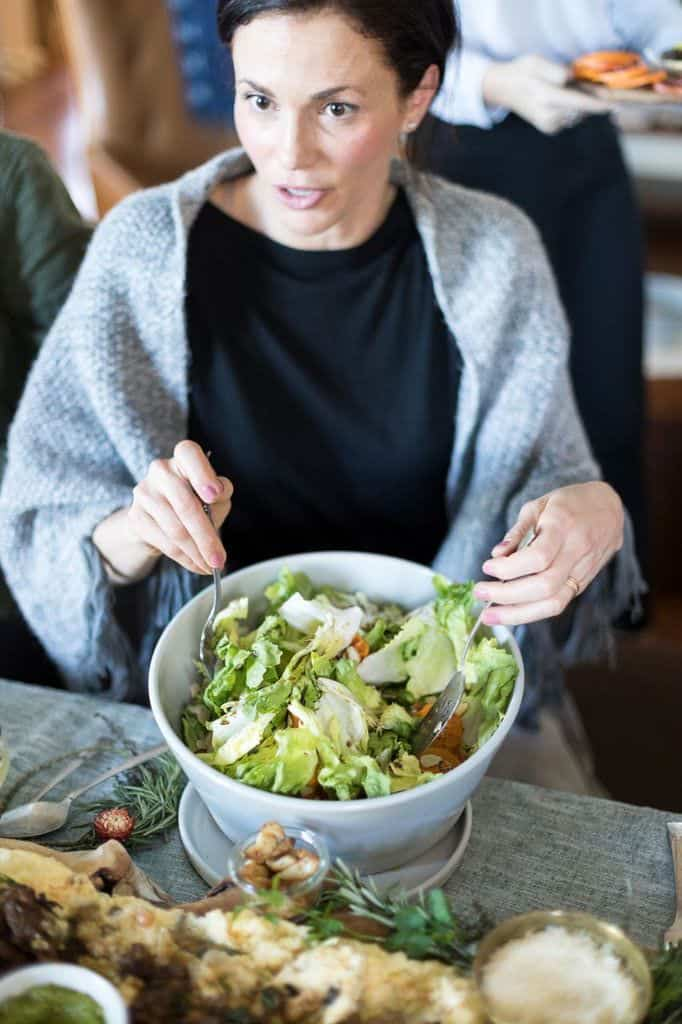 A woman in a black shirt and grey sweater scooping salad out of a large bowl.