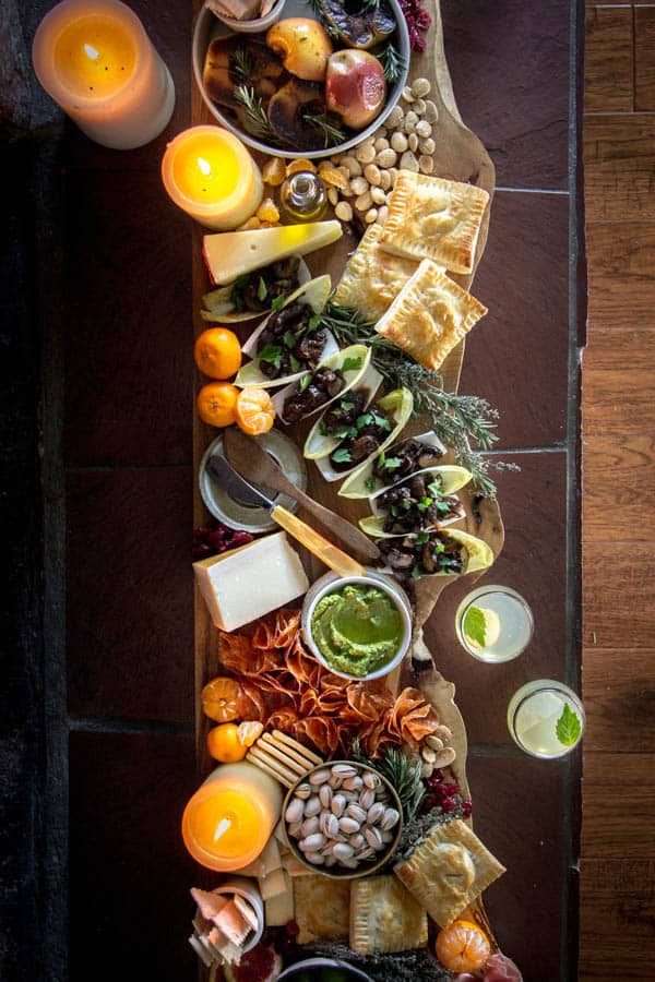 A long tray of appetizers sitting on a brown tiled ledge with candles around it.
