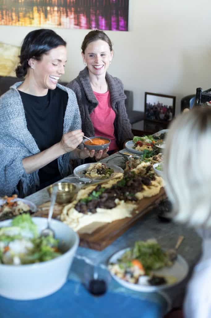 Two women sitting at a table laughing and spooning food on to their plates.