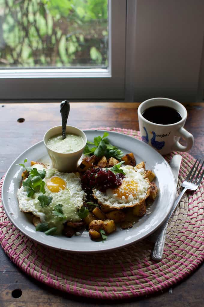 A plate of eggs and potatoes with green and red salsa sitting on a wooden table with a cup of coffee next to it.