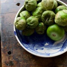 A blue and white bowl sitting on a wooden table filled with tomatillos.