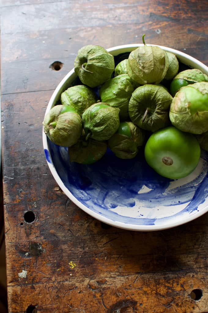A blue and white bowl sitting on a wooden table with tomatillos in it.