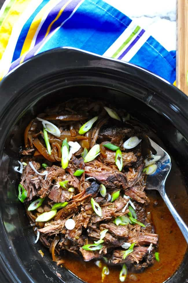 A black pot filled with shredded beef and sliced scallions over the top with a serving fork in the pot.