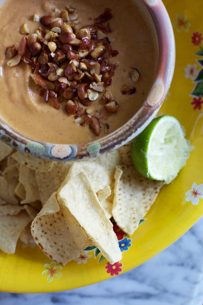 A bowl of peanut salsa with lots of chopped peanuts on top sitting in a bigger yellow bowl with tortilla chips and a lime wedge.